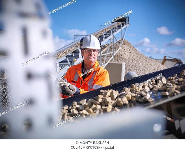 Worker examining stones on conveyor belt