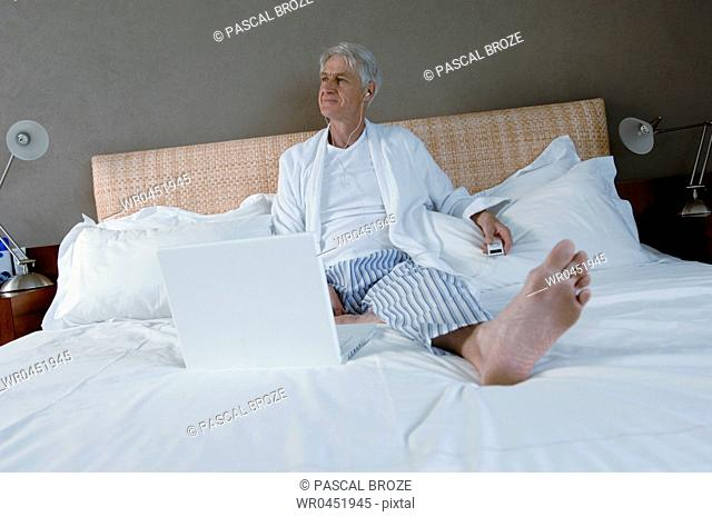 Senior man reclining on the bed and listening to music