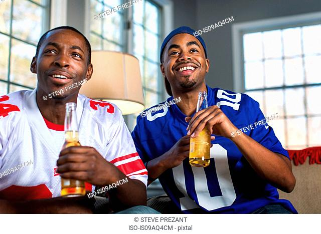 Two male friends drinking bottled beer whilst watching TV from sofa