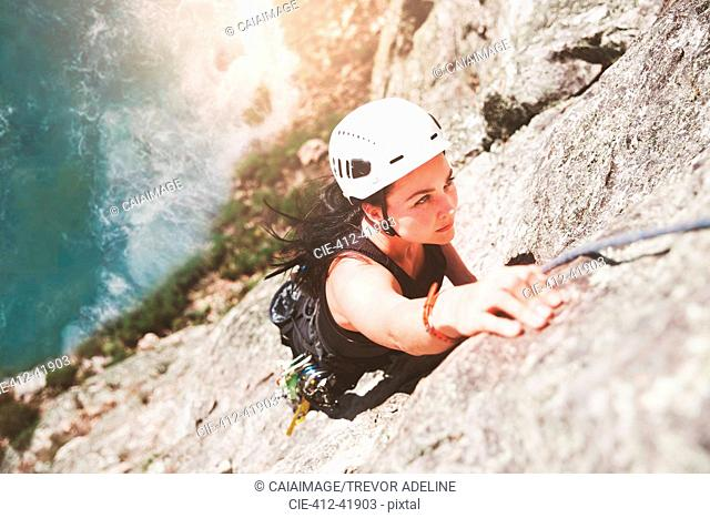 Focused, determined female rock climber scaling rock