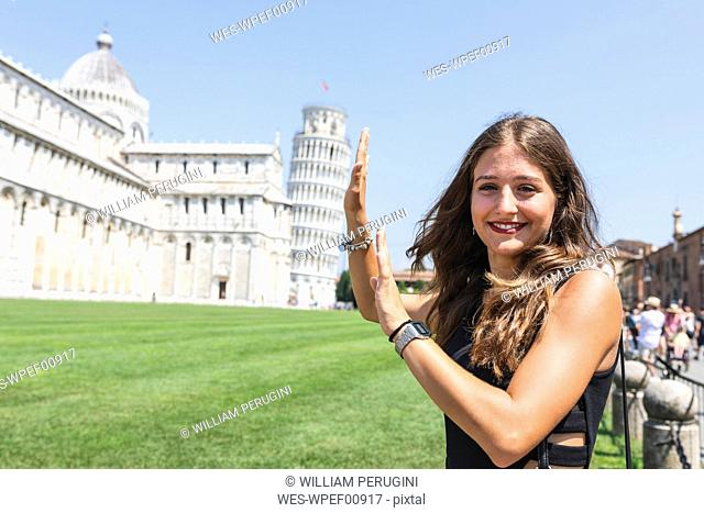 Italy, Pisa, portrait of young woman posing with the Leaning Tower in background
