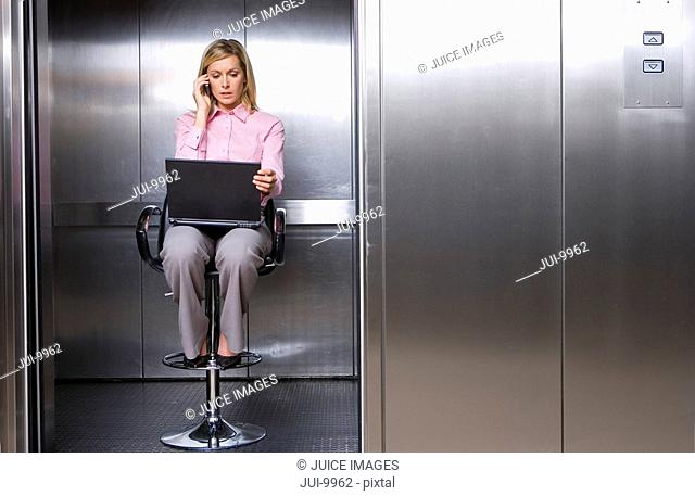 Young businesswoman using mobile phone on stool in lift, laptop computer on lap