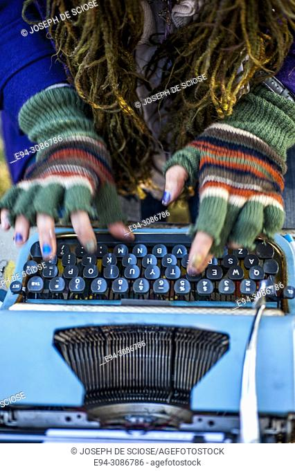 A woman's hands wearing fingerless gloves typing on an old manual typewriter