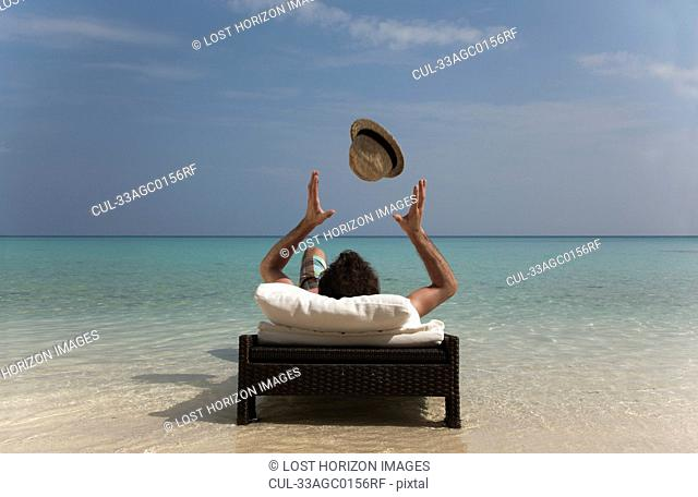 Man relaxing on daybed at tropical beach