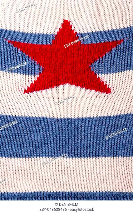 Woolen knitted clothing material, close up. Red star on striped pullover texture