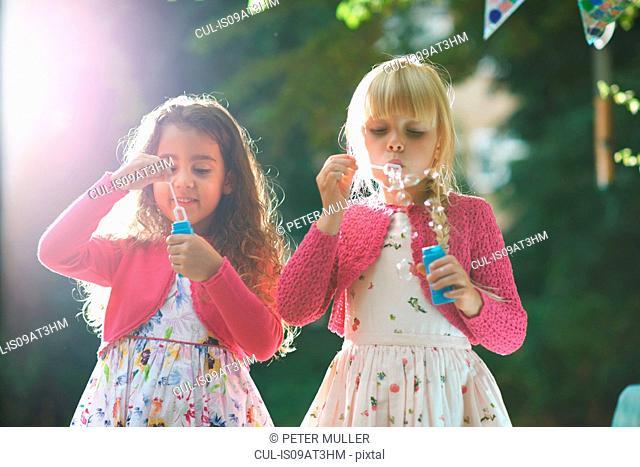 Two cute girls blowing bubbles in garden