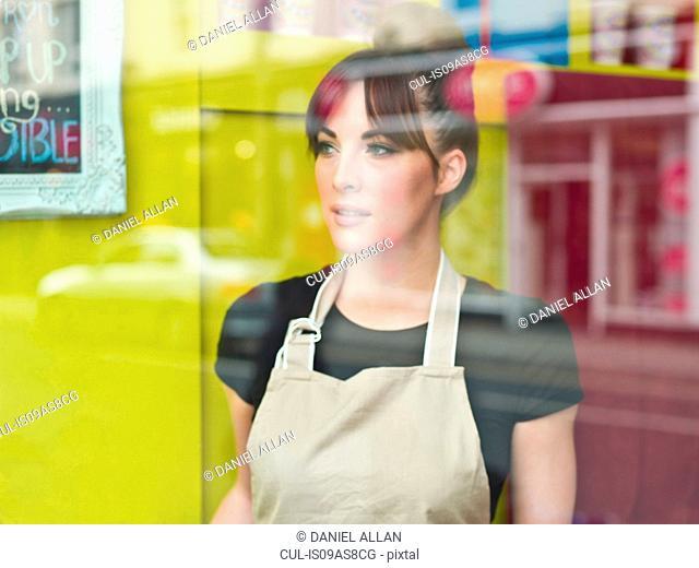 Portrait of young woman working in cake shop, taken through shop window