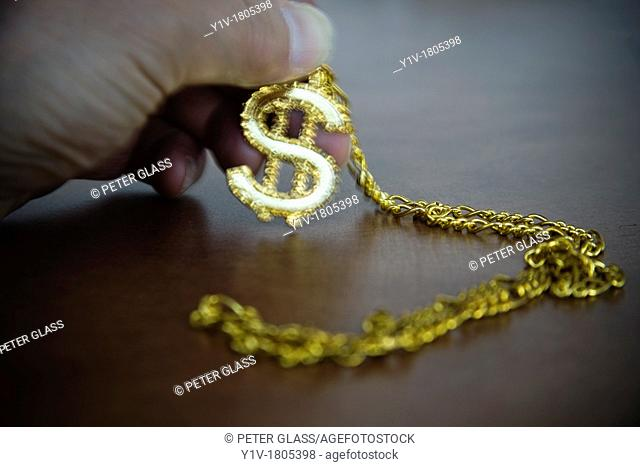 Man's hand holding an American dollar-sign necklace
