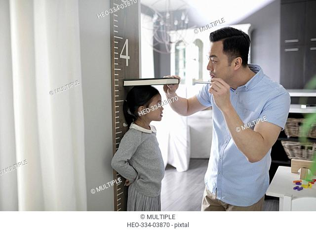 Father measuring height of daughter at wall