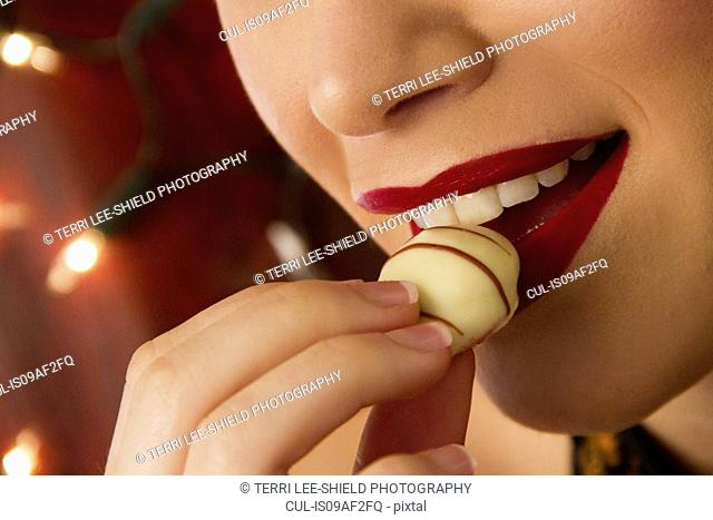 Cropped close up of young woman eating chocolate