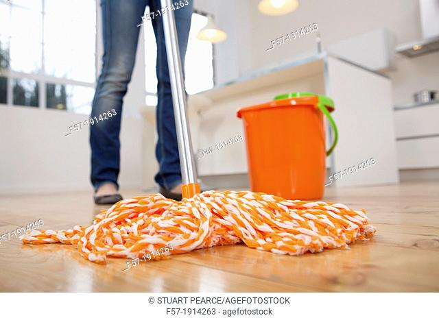 Young woman mopping her kitchen floor