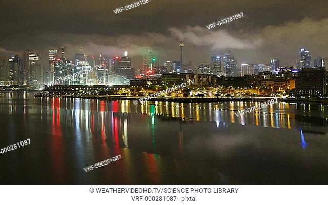 Sydney Harbour at night. Time-lapse footage of low-hanging fractostratus clouds swirling over Sydney Harbour and skyline at night in Sydney, New South Wales