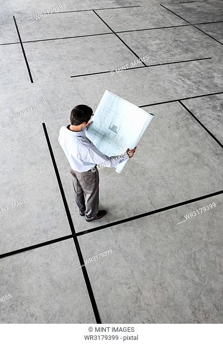 Caucasian businessman holding plans for a new office in a large empty raw office space