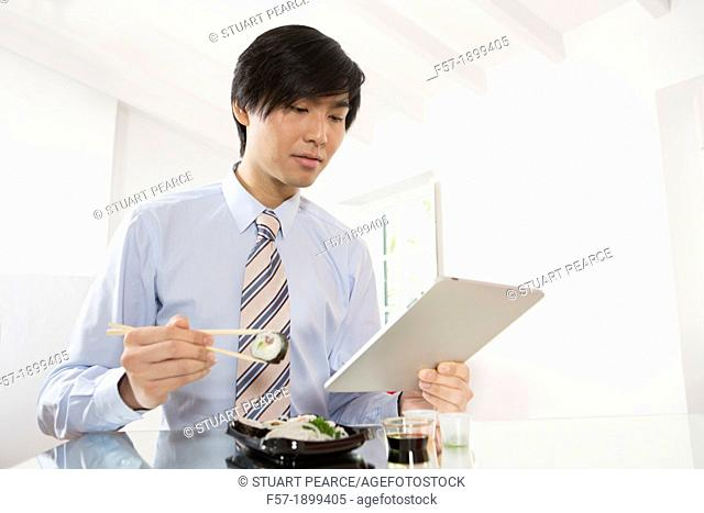 Young Asian businessman eating sushi while communicating on his Tablet computer