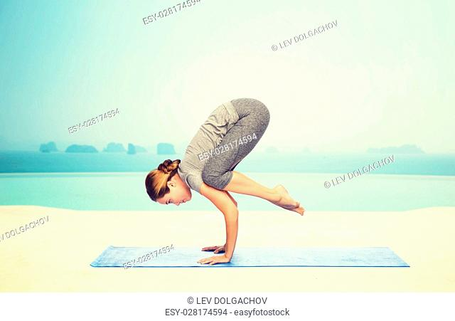 fitness, sport, people and healthy lifestyle concept - woman making yoga in crane pose on mat over infinity edge pool at hotel resort background