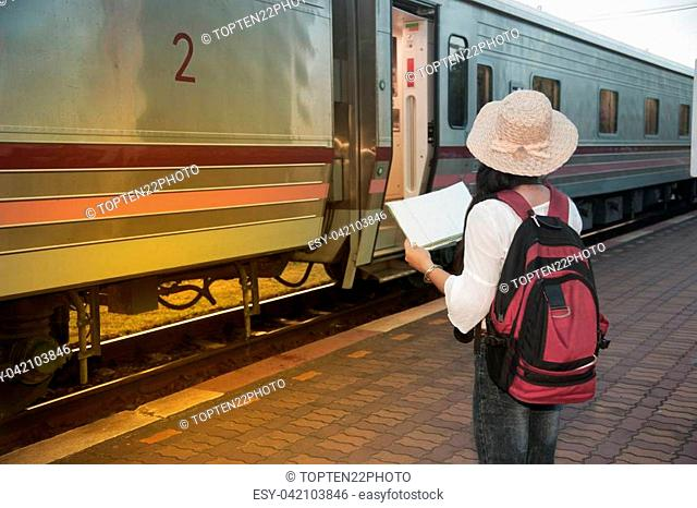 Pretty Asian female traveler joyful looking map and waiting train at railway station in Thailand