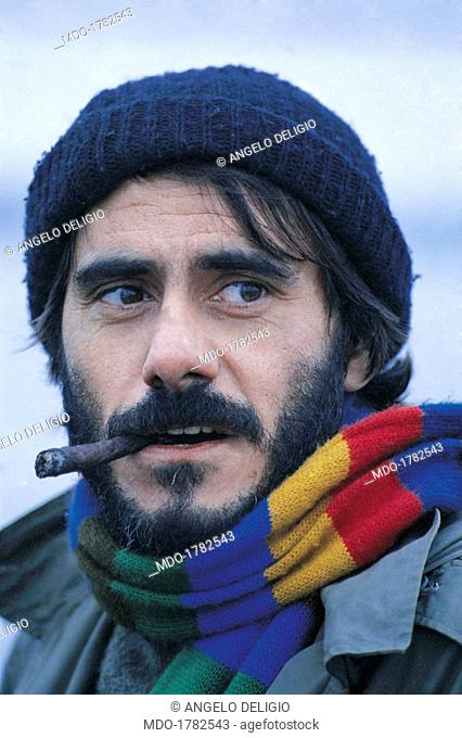 Roberto Vecchioni smoking the cigar. Italian singer-songwriter and writer Roberto Vecchioni with a cigar in his mouth wearing a wool hat and a multicolour scarf