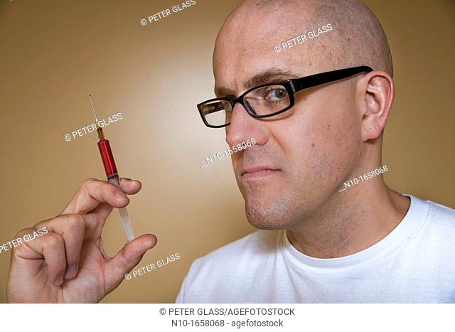 Middle-age bald man holding a syringe