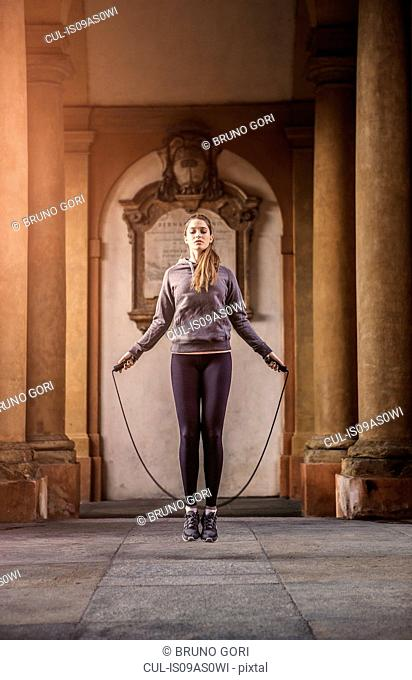 Front view of woman wearing sports clothes using skipping rope