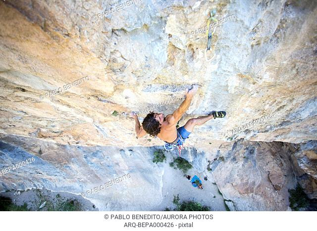 Young male climber challenging Collegats Gorge shirtless, Pobla de Segur, Lleida, Spain