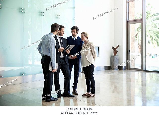Business associates collaborating using digital tablet