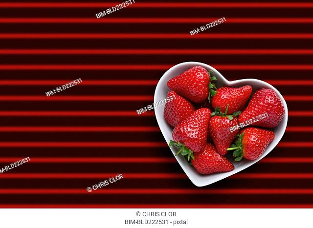 Strawberries in heart-shape bowl on red striped background