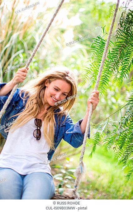 Happy young woman swinging on garden swing