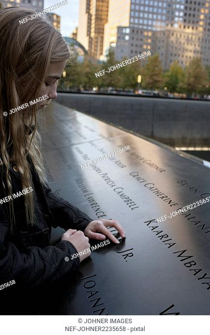 Girl reading text on memorial