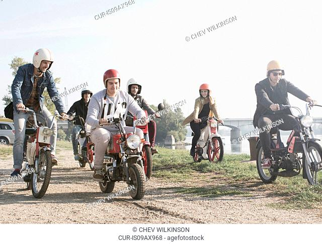 Group of friends riding mopeds beside lake