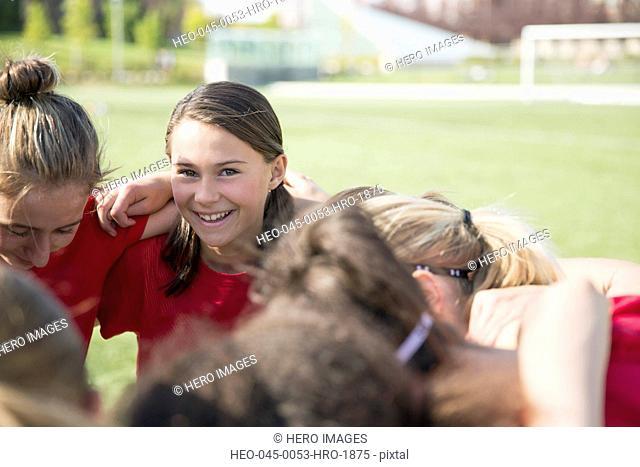 Girls soccer team in huddle on field