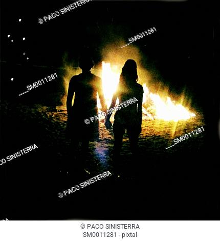 Backlit woman in the fires of the night of St. John, Alicante, Spain