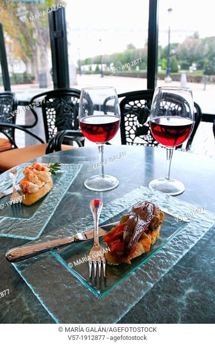 Spanish appetizer: tapas with rose wine in a terrace. Oriente Square, Madrid, Spain
