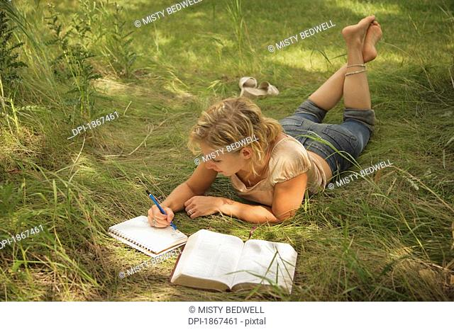 Woman laying in the grass and studying