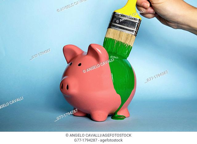 Woman's hand painting a piggybank with green paint