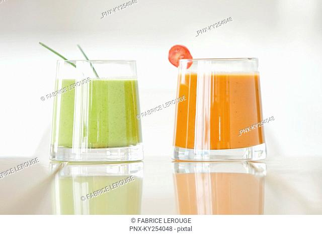 Close-up of two glasses of soups on a dining table