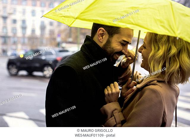 Happy business couple under umbrella in the city
