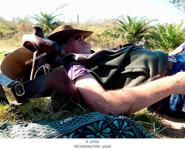 Senior man lying on back resting on saddle, Uruguay