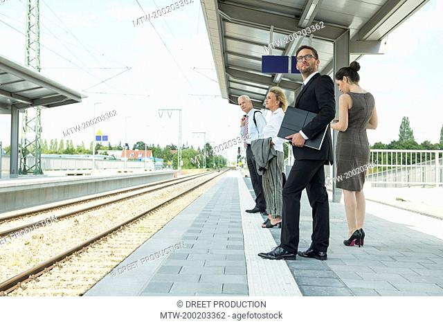 Four businessmen waiting for train