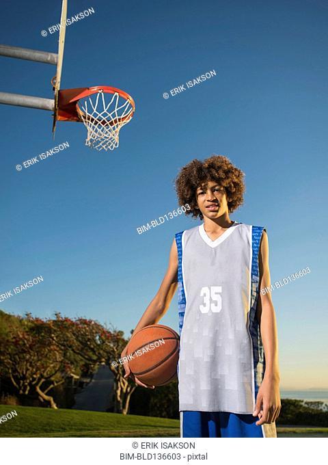 Black teenage boy holding basketball on court