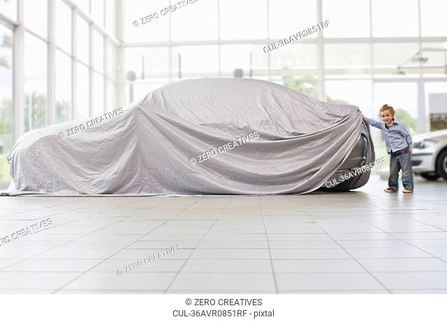 Girl peeking under cloth on car
