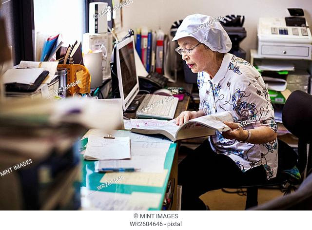 A mature woman at a desk in the office of a fast food unit and noodle production factory