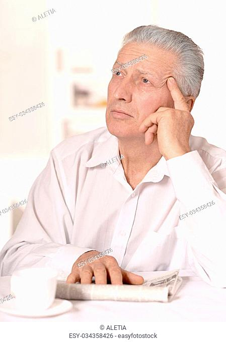 Attractive older man sitting at a table at home