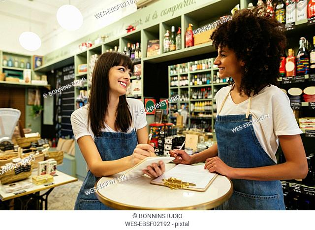 Two smiling women in a store taking notes