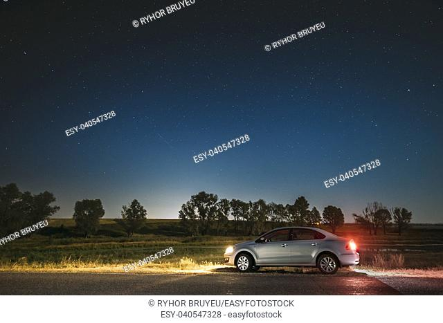 Blue Night Starry Sky Above Country Asphalt Road In Countryside. Sedan Car Parking Near Asphalt Road In Summer Night. Yellow Car Lights And Night View Of...