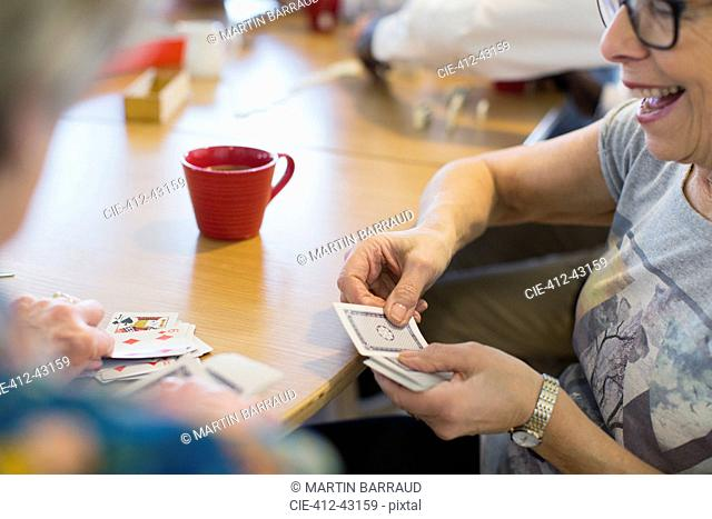 Senior woman playing cards with friend in community center