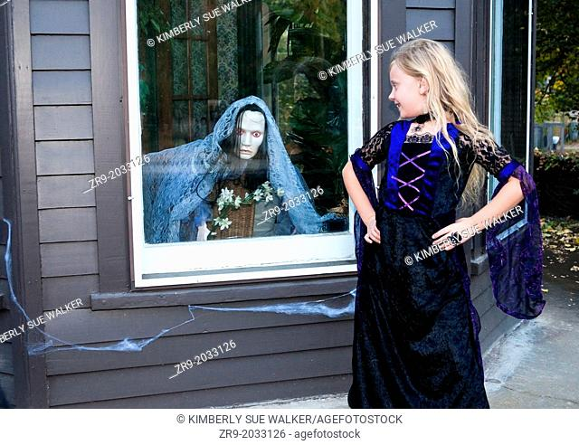 Girl in costume looks at scary witch decoration in window
