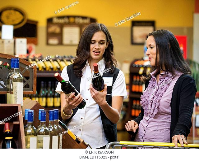 Worker talking to customer about wine in store