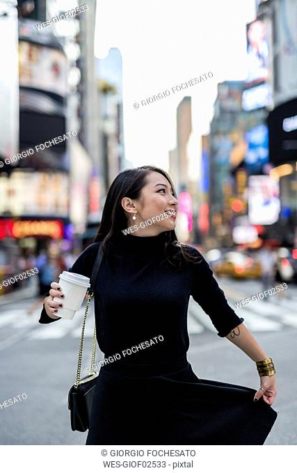USA, New York City, Manhattan, young woman dressed in black with coffee to go on the street