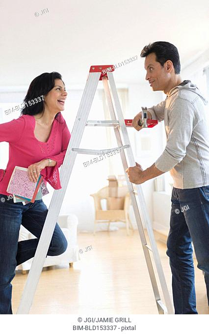 Couple talking at ladder during home remodeling