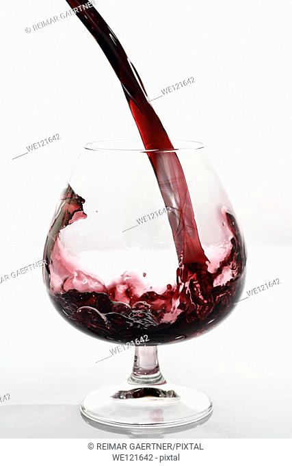 Frozen motion of port pouring into a glass snifter on a white background